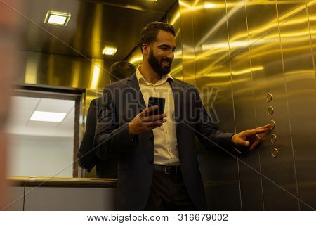 Positive Delighted Bearded Man Looking At The Button