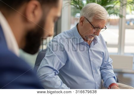 Serious Grey-haired Male Person Checking Data On Document