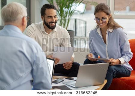 Group Of Pleased Colleagues That Looking At Laptop