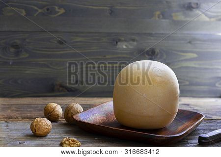 Round Head Of Cheese Kostromskoy On Textured Dark Wooden Background On The Square Plate With Several