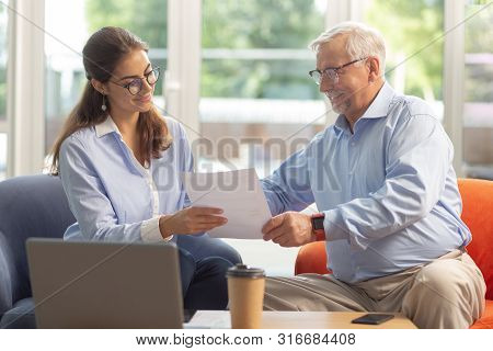 Attentive Mature Male Communicating With His Worker