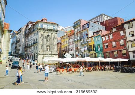 Porto, Portugal - August 31 2018: People On Promenade By River Douro On Sunny Day. The Embankment Is