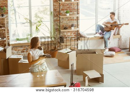 Young Couple Moved To A New House Or Apartment. Drinking Red Wine, Playing Guitar And Relaxing After