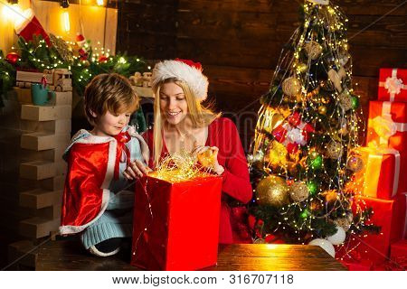 Family Holiday. Cozy Evening At Home. Mom And Kid Play Together Christmas Eve. Happy Family. Mother