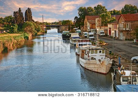 Saint-Gilles, Gard, Occitanie, France: landscape of the waterway with canal boats in the town at the edge of the Petite Camargue, between Arles and Nimes