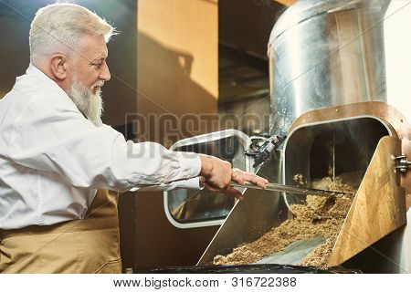 View From Side Of Professional Brewer Working At Beer Manufacturing Factory. Man Wearing White Shirt
