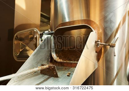 View From Side Of Modern Equipment Standing In Brewery. Professional Tank With Grist And Shovel At B