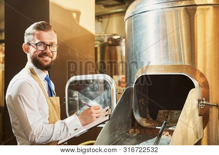 Cheerful Male Brewer Wearing Glasses Looking At Camera And Smiling While Writing Data In Folder. Man
