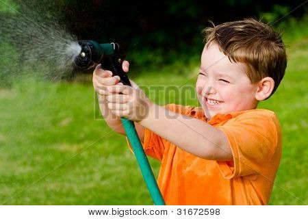 Child plays with water hose outdoors during summer or spring to cool off in hot weather