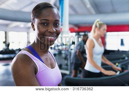 Close-up of African-american fit woman looking at camera while exercising on treadmill in fitness center. Bright modern gym with fit healthy people working out and training