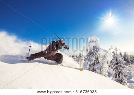 Skier Skiing Downhill During Sunny Day Fresh Snow Freeride. Extreme High Speed, Frosty Dust Scatters