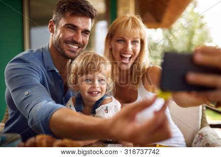 Cheerful parents with cute daughter taking selfie