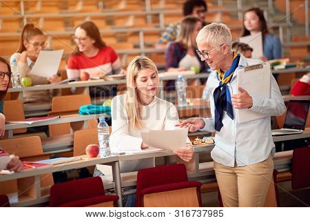 female lecturer with girl student in an exam in a classroom