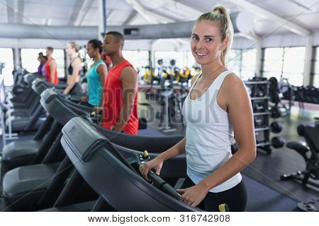 Portrait of Caucasian fit woman exercising on treadmill in fitness center. Bright modern gym with fit healthy people working out and training