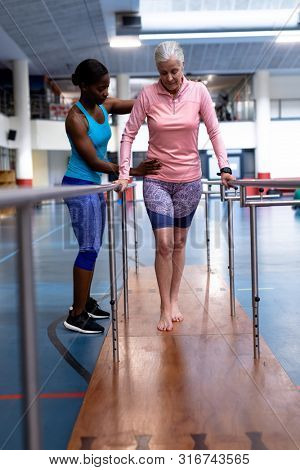 Front view of African-american female physiotherapist helping disabled Caucasian senior woman walk with parallel bars in sports center. Sports Rehab Centre with physiotherapists and patients working