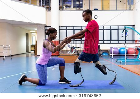 Side view of African-american physiotherapist helping disabled African-american man walk with prosthetic leg in sports center. Sports Rehab Centre with physiotherapists and patients working together