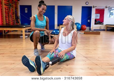 Front view of African-american female trainer talking with disabled Caucasian active senior woman in sports center. Sports Rehab Centre with physiotherapists and patients working together towards