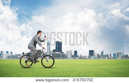 Businessman With Megaphone On Bike At Sunny Day. Marketing And Advertising Campaign. Manager In Busi