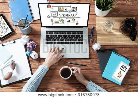 Top View Modern Office Workspace With Woman Hands. Flat Lay Wooden Desk With Laptop Keyboard And Cup