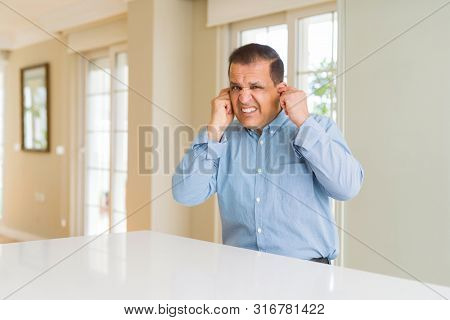 Middle age man sitting at home covering ears with fingers with annoyed expression for the noise of loud music. Deaf concept.