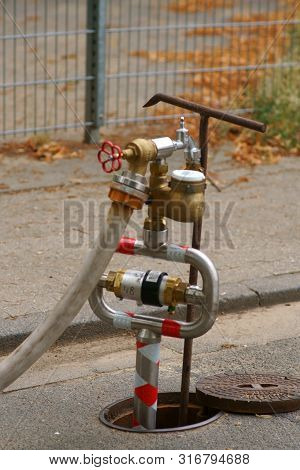 A Water Pumping Station With Water Pipes And A Water Meter At The Curb Of A Walkway.    A Water Pump
