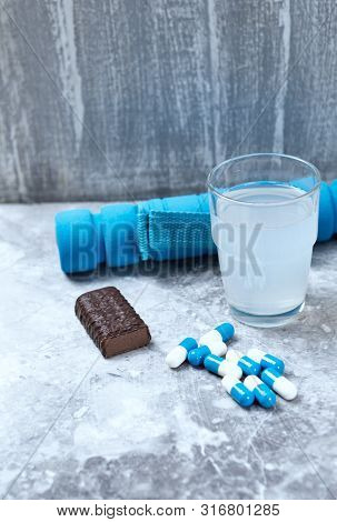 Bcaa (amino Acids) Drink, Creatine Capsules And Blue Dumbbells In Background. Sport Nutrition. Stone