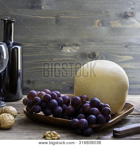 Round Head Of Cheese Kostromskoy On Textured Dark Wooden Background On The Square Plate With Grapes