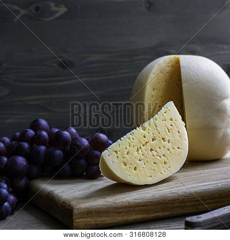 Round Head Of Cheese Kostromskoy With Cut Piece On Wooden Background On Square Plate With Grapes. Sq