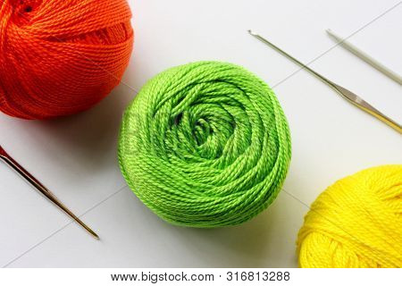 Crochet Yarn Background. Yarns Green, Red, Yellow Colors On White Background With Crochet Hooks. Kni