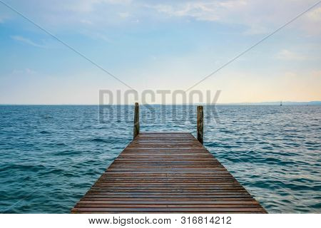 Landscape with the image of a pier on Garda lake in Italy