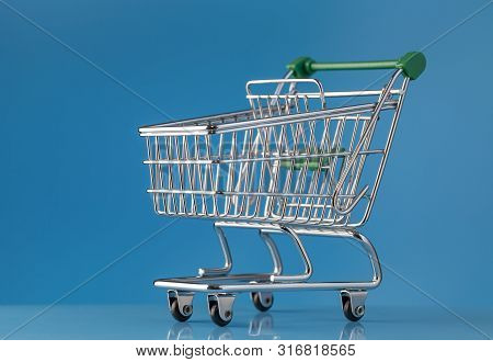 A Shiny New Shopping Cart On A Blue Background