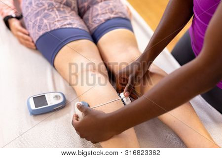 Close-up of African-american physiotherapist applying electro stimulation to active Caucasian senior woman in sports center. Sports Rehab Centre with physiotherapists and patients working together