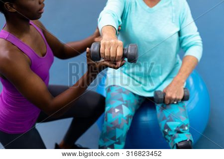 Close-up of African-american female trainer assisting disabled Caucasian senior woman to exercise with dumbbell in sports center. Sports Rehab Centre with physiotherapists and patients working
