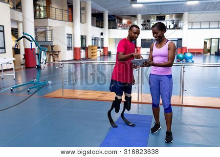 Front view of African-american female trainer and disabled African-american man discussing over digital tablet in sports center. Sports Rehab Centre with physiotherapists and patients working together