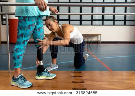 Beautiful female physiotherapist helping disabled senior woman walk with parallel bars in sports center. Sports Rehab Centre with physiotherapists and patients working together towards healing