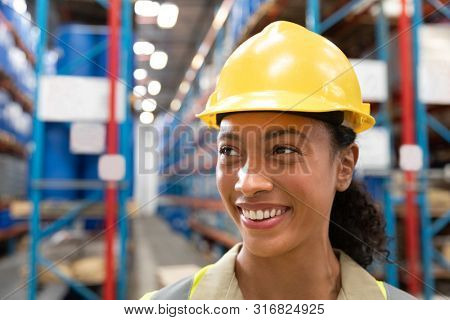 Close-up of female staff with hardhat smiling in warehouse. This is a freight transportation and distribution warehouse. Industrial and industrial workers concept