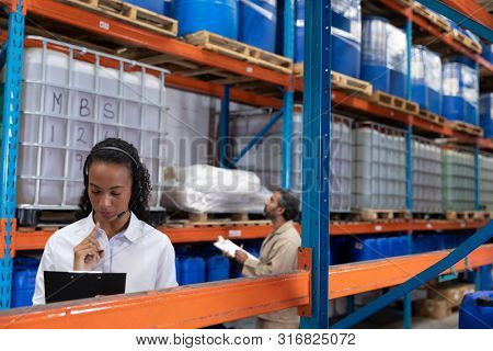 Female manager talking on headset while writing on clipboard in warehouse. This is a freight transportation and distribution warehouse. Industrial and industrial workers concept