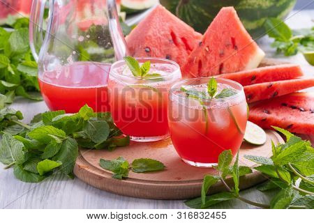 Summer watermelon drink. Cold watermelon drink with lime and mint on a wooden board. Watermelon smoothie. Watermelon juice with mint and lime. Refreshing red summer juice