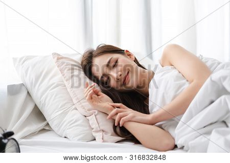 Portrait Of Sleeping Young Asia Woman Enjoy And Relax Lying On The Bed With Close Eyes In Bedroom At