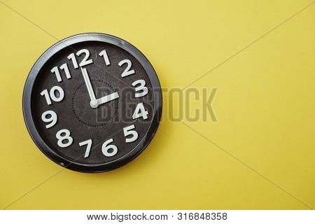 Black Round Clock Showing Eleven O'clock On Yellow Background