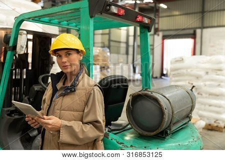 Beautiful female worker looking at camera while working on digital tablet in warehouse. This is a freight transportation and distribution warehouse. Industrial and industrial workers concept