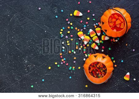 Halloween Background With Halloween Symbols Sweet Candy Corn, Colorful Confetti And Pumpkin Bucket F