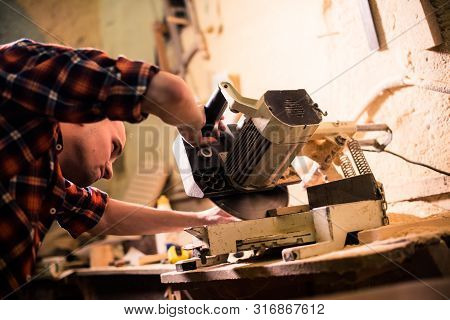 Young Handsome Joiner Working With Wood In His Carpentry Workshop