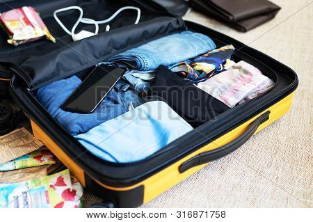 An Open Suitcase With Men's Clothing, Packed For A Business Trip.
