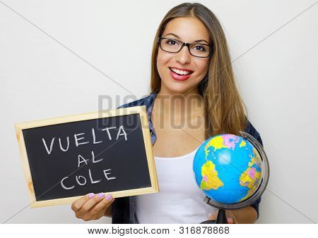 Latin Young Female Teacher Holding Globe And Blackboard With Spanish Written