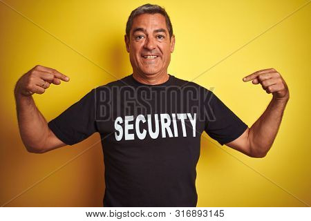 Middle age safeguard man wearing security uniform over isolated yellow background very happy pointing with hand and finger