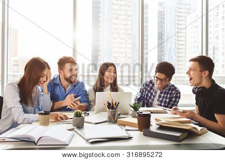 University Students Sitting Together At Table With Books And Laptop, Doing Group Study In Library, F