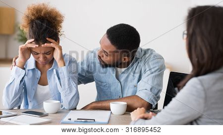 Bankruptcy And Investment Mistakes. African American Husband Comforting His Crying Wife On Meeting W