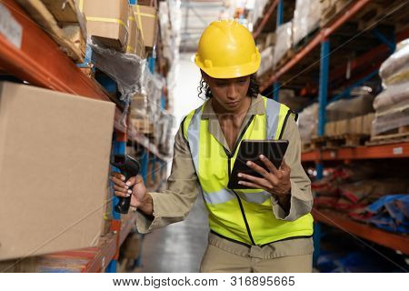 Front view of female worker scanning package with barcode scanner while using digital tablet in warehouse. This is a freight transportation and distribution warehouse. Industrial and industrial