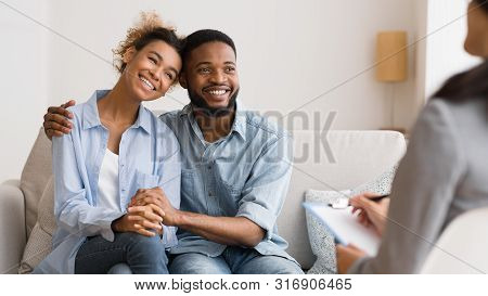 Successful Couples Therapy. Afro Spouses In Love Hugging After Making Up Quarrel At Counselors Offic